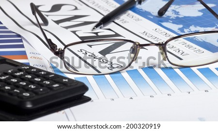 Glasses, pen and calculator on business documents background. - stock photo