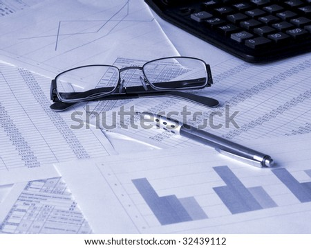 Glasses, pen and calculator on financial documents. Toned blue. Shallow DOF. - stock photo
