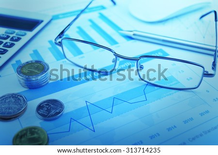 Glasses, pen and coin on growth financial graph, accounting background, blue tone