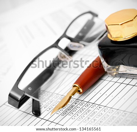 Glasses, pen and ink on documents. - stock photo