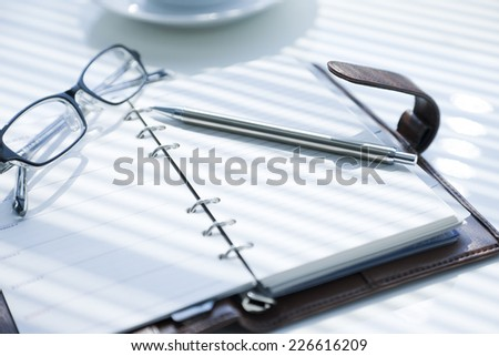 Glasses, pen, and notebook on a desk