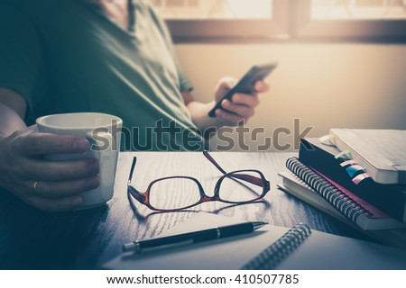 Glasses put down on table beside notebooks and pen while young freelance worker using smart phone and holding coffee cup in morning time on work day, Working at home concept with vintage filter effect - stock photo