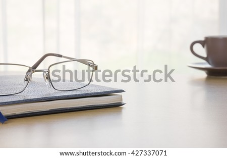 Glasses put on book and coffee cup on the desk by nature light from window - stock photo