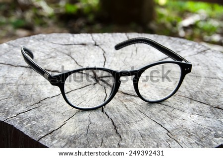 Glasses resting on a log.