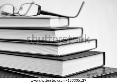 Glasses resting on open book - stock photo