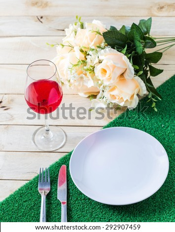 Glasses set with dinner table,dinner table with rose ,dish ,knife and fork set - stock photo