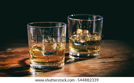 Glasses whiskey and ice cubes on wooden background