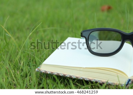 Glasses with a notebook on the grass.