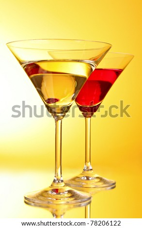 glasses with alcoholic beverage on  yellow-brown background