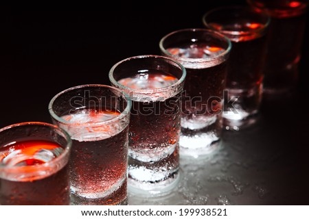 Glasses with an alcoholic drink on a damp glass table - stock photo