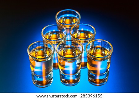 Glasses with an alcoholic drink on a glass table