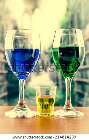 glasses with blue and green liquor alcohol cocktail beverage liquid juice and yellow shot on wooden table