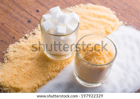 Glasses with brown granulated sugar and white refined sugar - stock photo