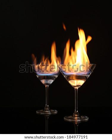 Glasses with burning alcohol on black background - stock photo