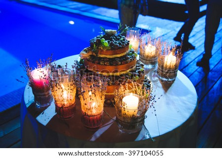 glasses with candle and lavender and cake in blue light