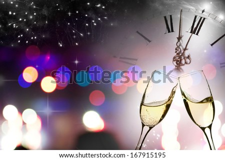 Glasses with champagne against fireworks and clock close to midnight  - stock photo