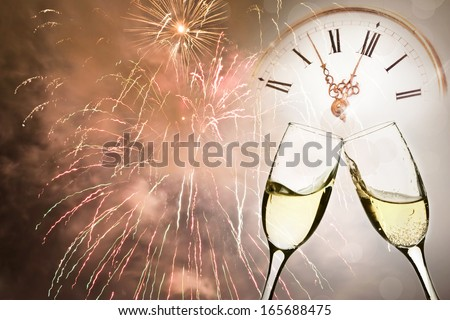 Glasses with champagne against holiday lights and clock close to midnight - stock photo
