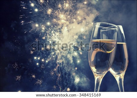 Glasses with champagne against night sky with fireworks  - stock photo