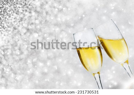Glasses with champagne against sparkling holiday lights - stock photo