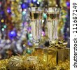 Glasses with champagne and a gift. Christmas objects, the bright lights and colors - stock photo