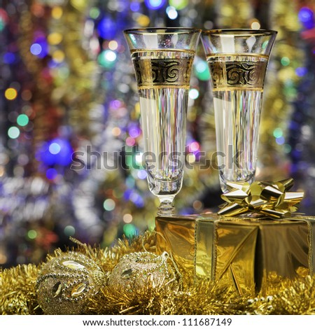 Glasses with champagne and a gift. Christmas objects, the bright lights and colors