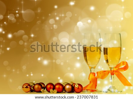 Glasses with champagne and Christmas decoration against holiday lights