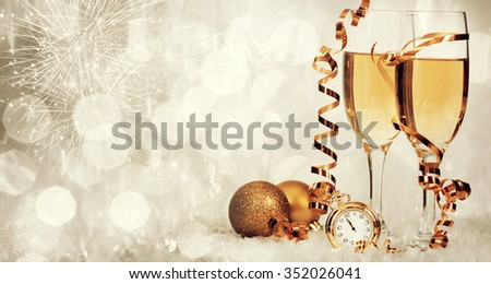 Glasses with champagne and Christmas decoration on sparkling holiday background - stock photo