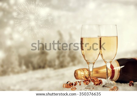 Glasses with champagne and Christmas decoration on winter background - stock photo