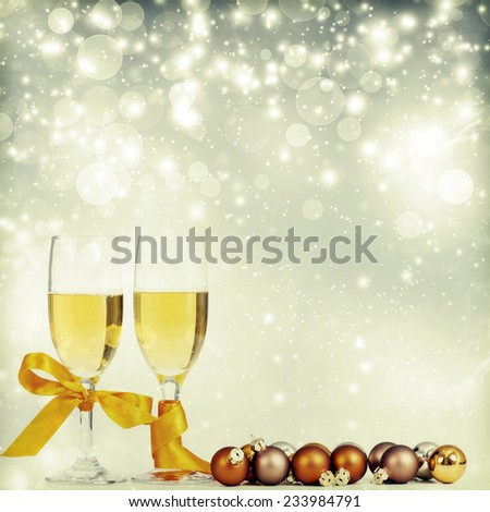 Glasses with champagne and christmas decorations on sparkling background