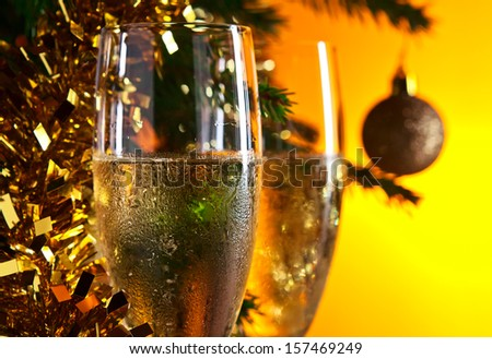glasses with champagne and Christmas ornaments , focus on foreground
