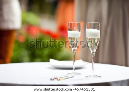Glasses with champagne and foam stand on the white table - stock photo