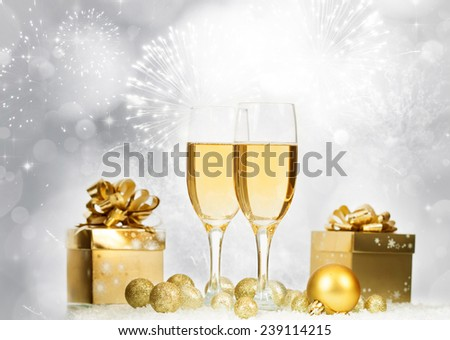 Glasses with champagne and gift box against fireworks and holiday lights - stock photo
