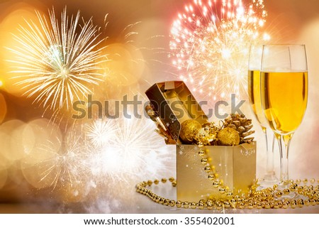 Glasses with champagne and golden gift box with Christmas balls against fireworks and holiday lights - stock photo