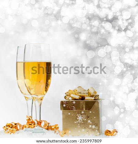 Glasses with champagne gift box over sparkling holiday background - stock photo