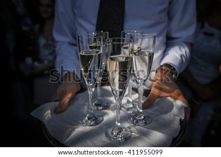 Glasses with champagne on a tray - stock photo