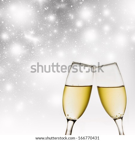 Glasses with champagne on light grey background of holiday lights - stock photo