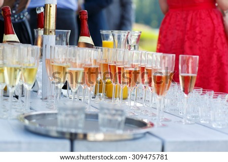Glasses with champagne, orange juice and wine on summer wedding - stock photo