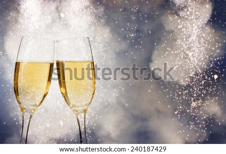 Glasses with champagne over fireworks and sparkling holiday background - stock photo