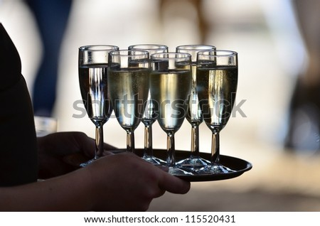 glasses with champagne served on a tablet - stock photo