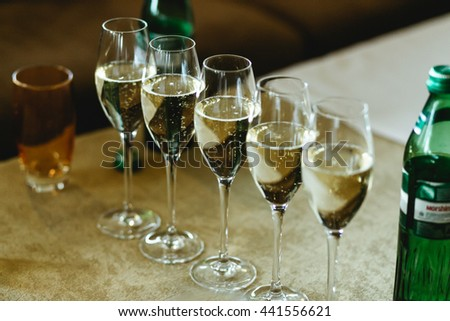 Glasses with champagne stand in a ray on the table