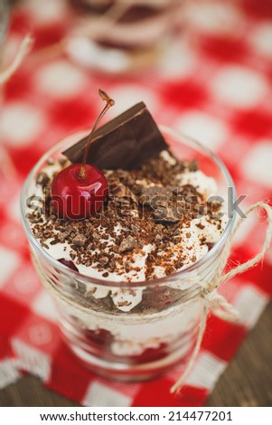 Glasses with cherries and chocolate parfait with whipped sour cream. Shallow dof. Delicous redcurrant sundaes or desserts? glasses of colorful layered berry coulis, ice cream or frozen yoghurt - stock photo