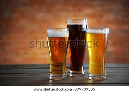 Glasses with different sorts of craft beer on brick wall background - stock photo