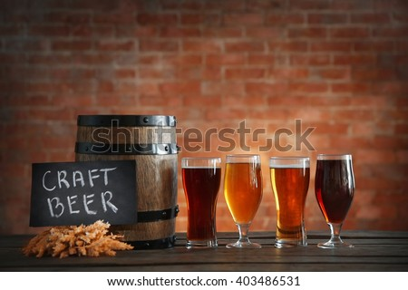 Glasses with different sorts of craft beer, wooden barrel and barley ears on brick wall background - stock photo