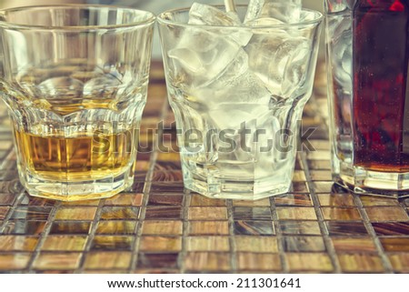 Glasses with drinks on the table in the cafe. Whiskey, ice and Cola - stock photo