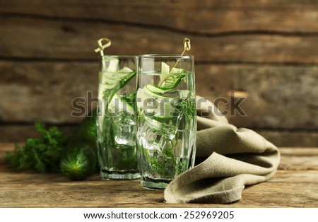 Glasses with fresh organic cucumber water on wooden table - stock photo