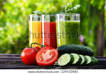 Glasses with fresh vegetable juices in the garden. Detox diet. - stock photo