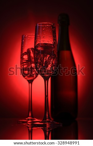 glasses with ice and a bottle of champagne on a red background