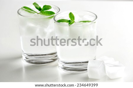 Glasses with ice cubes isolated on white - stock photo