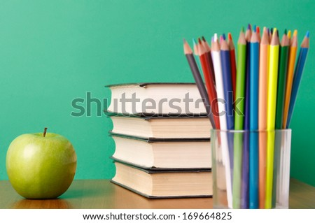 Glasses with paencils and green apple, isolated on green background