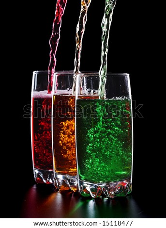 Glasses with pouring colorful sparkling drinks isolated on black background - stock photo